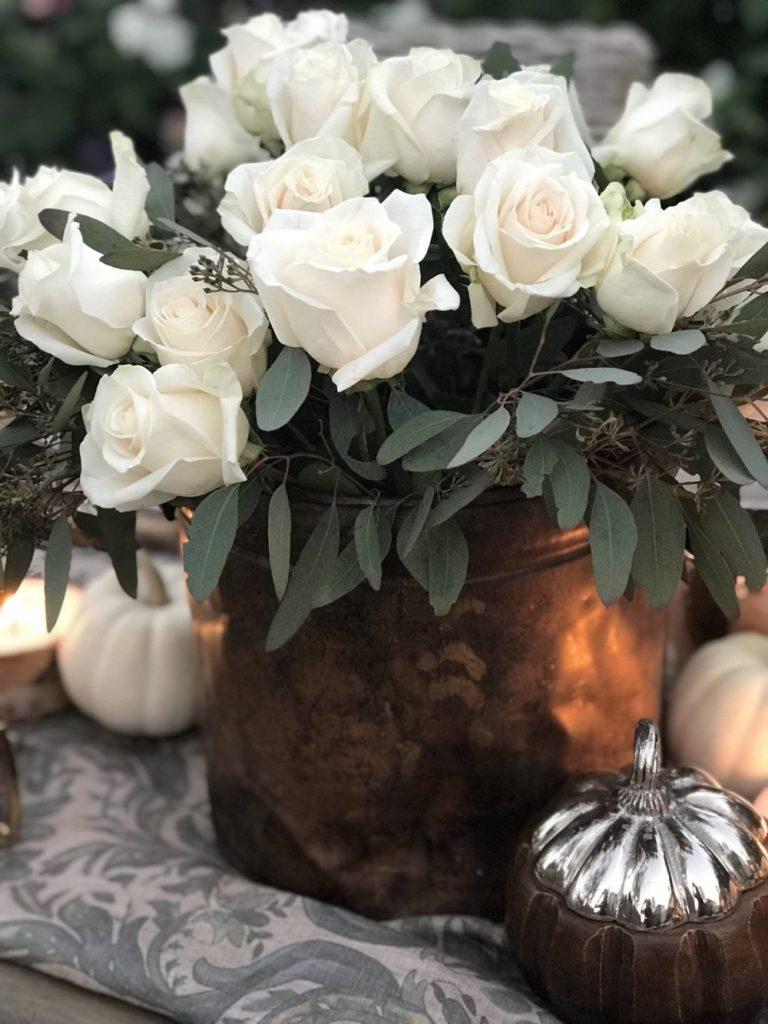 White rose centerpiece in copper bucket