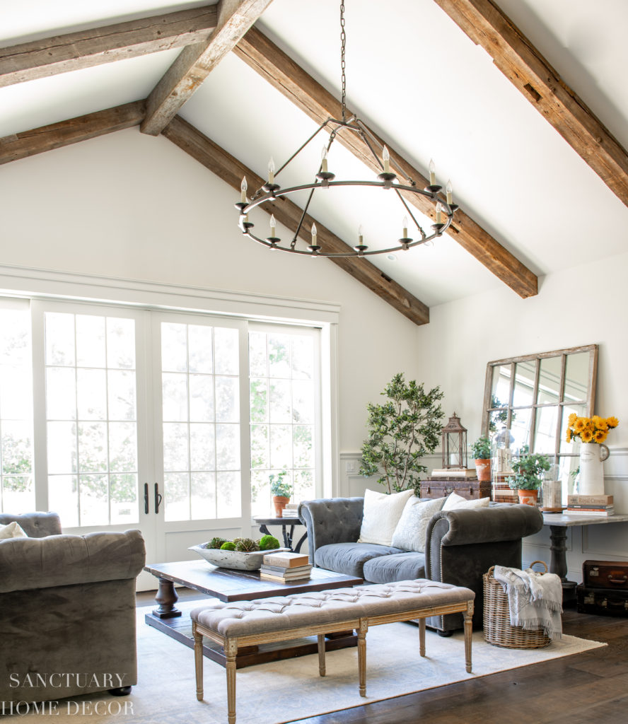 Rustic elegant living room with chesterfield couches and yellow decor accents. Faux greenery.