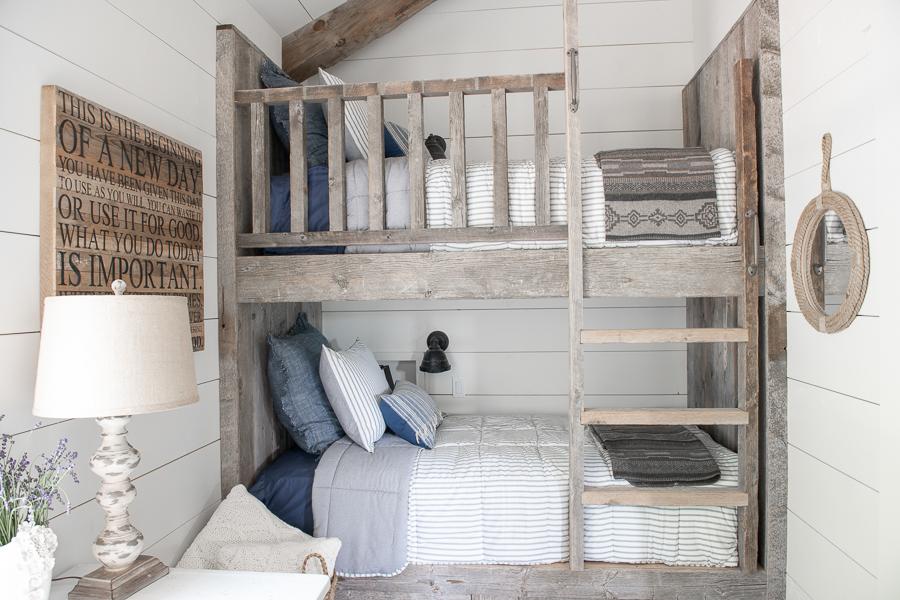 Reclaimed barn wood bunk beds in kid's bunk room. Shiplap walls.