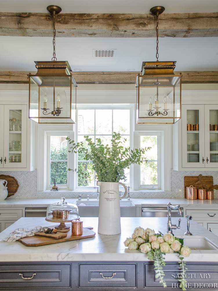 5 Minute Fall Decorating Tips-White country kitchen with pendant lights and glass front cabinets. White marble countertops.