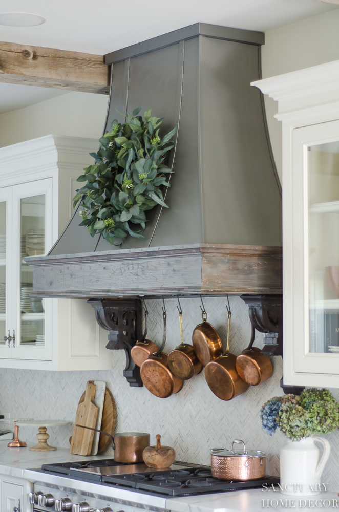 5 Minute Fall Decorating Tips-White country kitchen with pendant lights and glass front cabinets. White marble countertops-Zinc Range hood