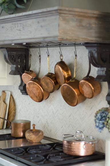 Hanging copper pots behind range.